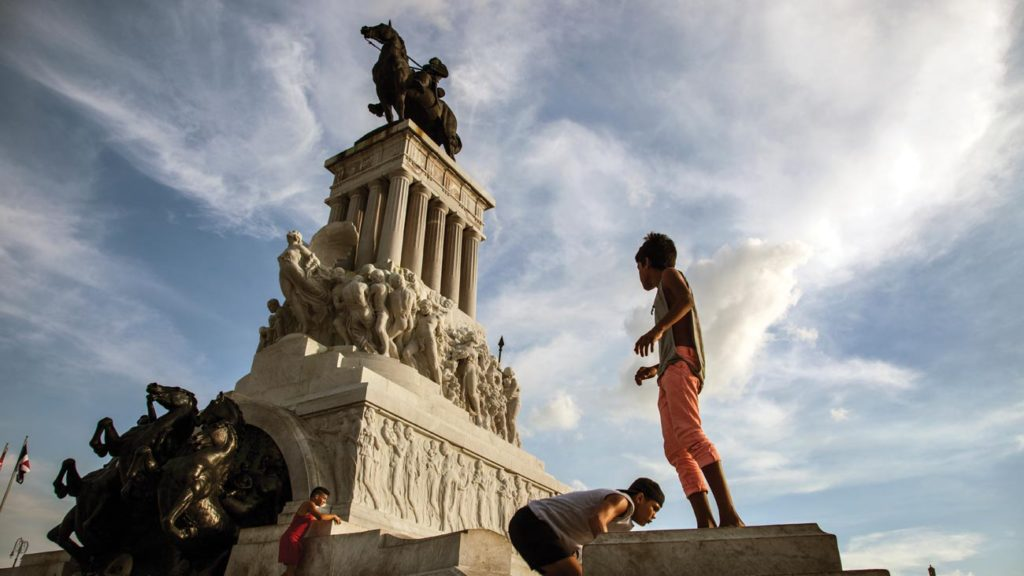 Boys playing parkour, a form of tag, around the Monumento a Máximo Gómez, erected in bronze and marble to pay homage to one of the great military leaders of Cuba's nineteenth-century wars of independence