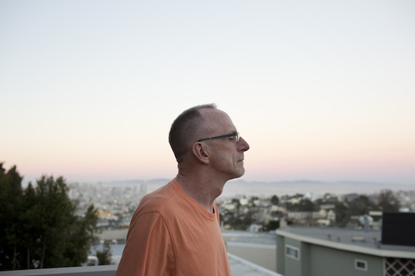 Kevin VandenBergh, a long-term AIDS survivor, looks at the city from the balcony of his apartment in San Francisco, Calif. on September 21, 2015. VandenBergh uses support groups and volunteering to combat the isolating aspects of being a long-term survivor. Photo by Tim Hussin