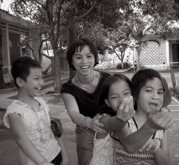 Amazin LeThi shares a lighthearted moment with children at an orphanage in Vietnam. Photo courtesy Amazin LeThi