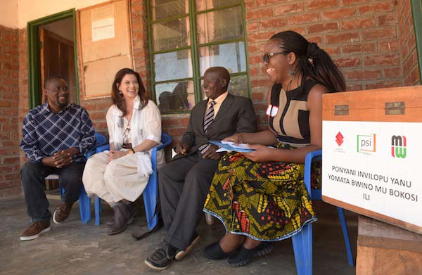 PSI Global Ambassador Debra Messing meets with traditional leader and community gate-keeper Windolosi Ntchona (second to right) at the steps of Chifunga Good Future Organization (GOFO) to discuss how making HIV testing easier and more accessible can lead to getting people on treatment sooner. Windolosi is the senior village headman of Chapita and advocates for the distribution of HIV self-testing kits in his community. Photo by Eric Gauss