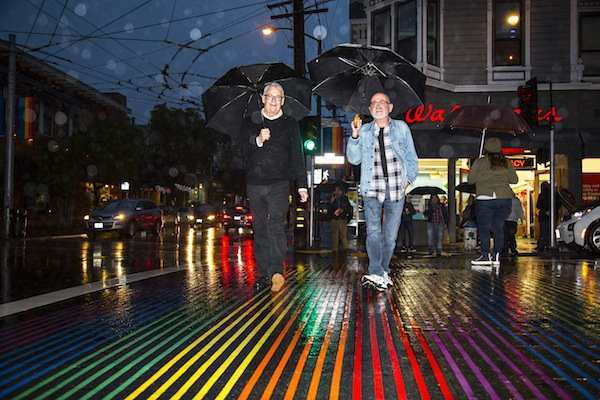 Cleve Jones and writer Hank Trout dodge the rain, traversing the rainbow crosswalk at 18th and Castro Streets in San Francisco.
